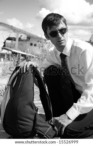 The Young man with parachute on background of the airplane-biplane.