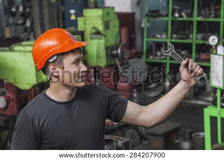 The young man working at the old factory on installation of equipment in a protective helmet
