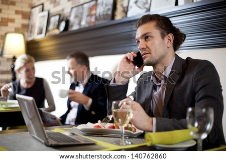 The young man working with the laptop uses phone. Its colleagues conduct conversation - stock photo