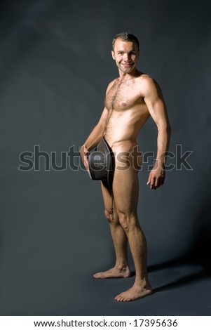 The young naked man poses in studio - stock photo