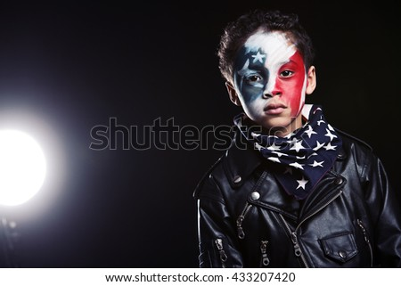 The Young Patriot.  A young, mixed race boy wearing red, white and blue face paint, a flag scarf around his neck and a leather jacket.  A bright light shining in the background.