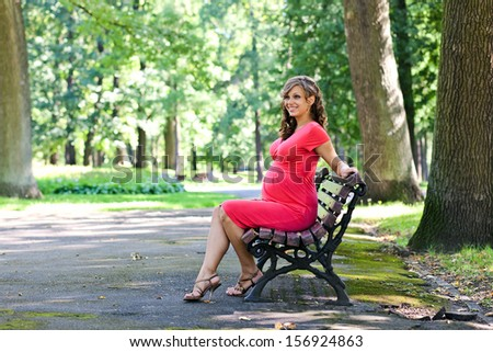 The young pregnant woman has a rest on a bench in park