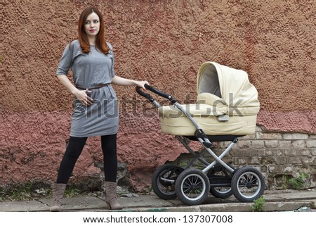 The young pretty caucasian woman with a baby carriage a cradle against an old wall - stock photo