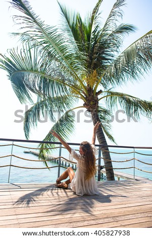 The young quite stylish sensual woman posing on the amazing tropical beach with the blue ocean enjoy her holiday and a windy summer sunny day. Dressed in a white dress. - stock photo