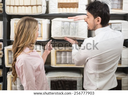 The young salesman tells the customer about quality mattresses in the store.