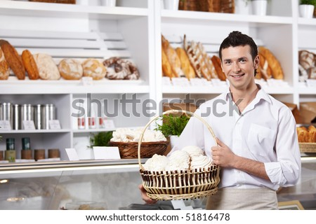 The young seller holds a basket with cakes in shop - stock photo