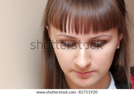The young serious woman looks down indoor - stock photo