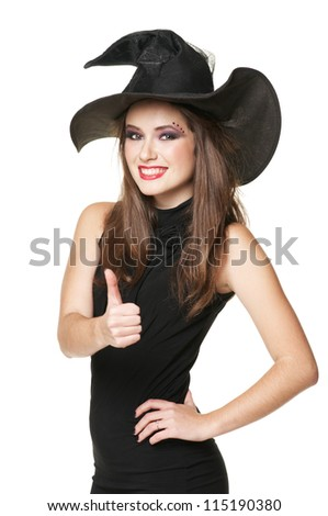 The  young smiling witch is thumb up in a dress - stock photo
