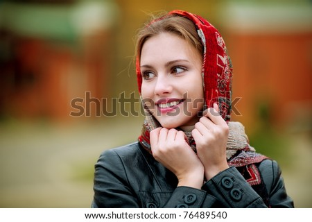 The young smiling woman in a red scarf on walk