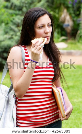 The young student in park with a sandwich in a hand