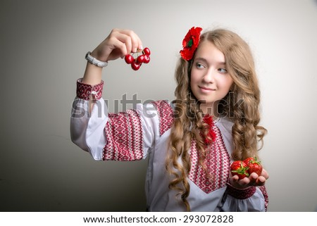 The young Ukrainian girl looking at red fruit - stock photo