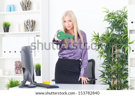 the young woman at office holds big a green key - stock photo
