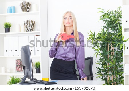 the young woman at office holds big a red key - stock photo