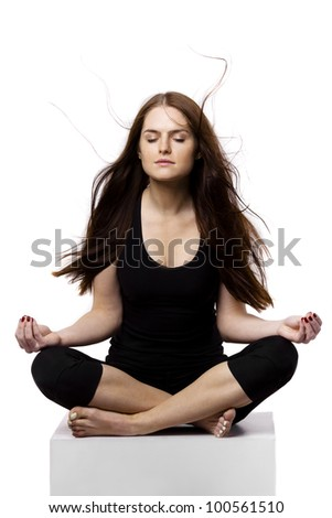 The young woman dressed in black sitting cross-legged, eyes closed and relax. The wind blows on her hair. - stock photo
