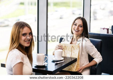 The young woman gives a gift to a young girl in the cafe