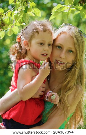 The young woman holds the little girl on hands - stock photo