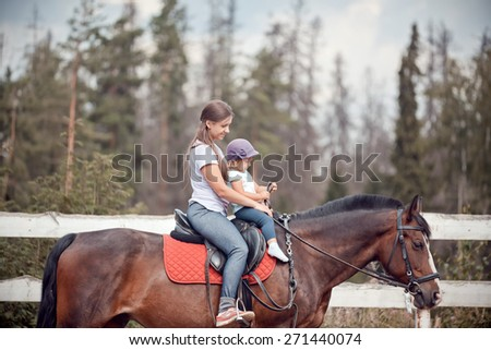 The young woman horseback riding at summer evening