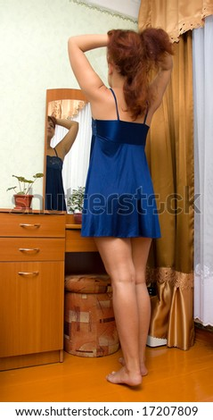 The young woman in a dark blue peignoir does a hairdress facing to a mirror in a room