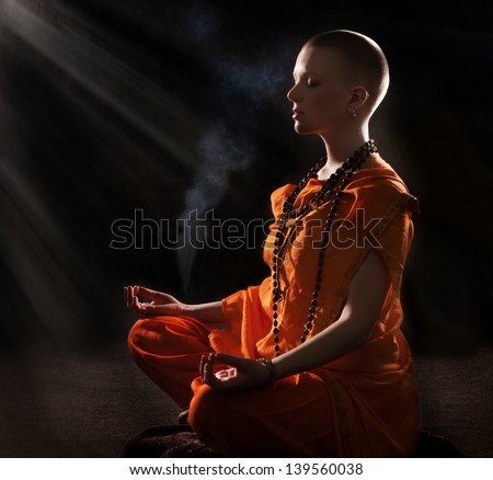 The young woman in orange robers in meditation - stock photo