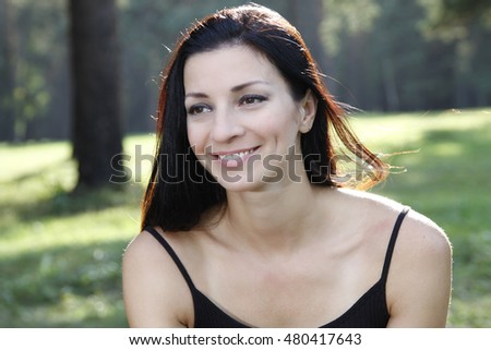 the young woman in park, thoughtfully looks afar, happily smiles