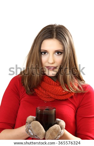 the young woman in red clothes and mittens holds a cup of fragrant tea in hand - stock photo