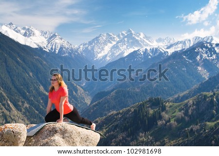 The young woman is doing a yoga asana Pose of pigeon on the summit. On the background is a range of high tops of mountains. - stock photo