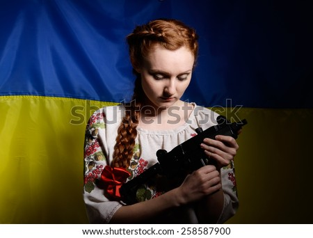 The young woman is holding a uzi gun against the national Ukrainian flag. She is wearing a shirt embroidered. Her red hair are plaited with a red ribbon. - stock photo