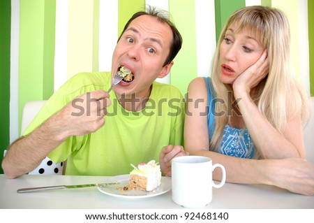 The young woman looks as the man eats a cake