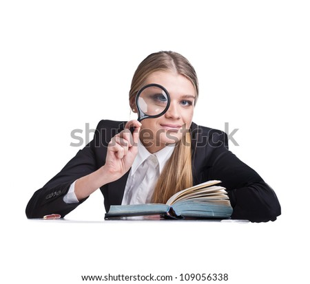 the young woman looks through a magnifying glass