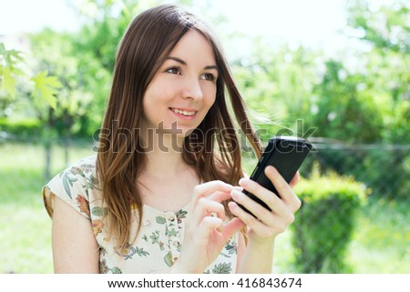 The young woman on outdoors with a smartphone - stock photo