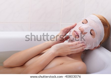 The young woman puts a nutritious mask for the person - stock photo