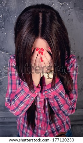 The young woman shut the face with the hands - stock photo