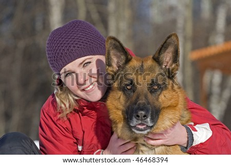 The young woman sits embracing the big dog of breed a German shepherd