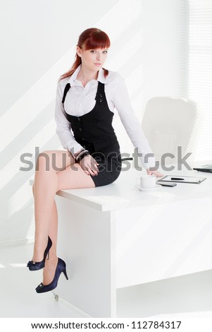The young woman sits on a table at office