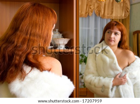 The young woman tries on a white mink fur coat before a mirror in a room