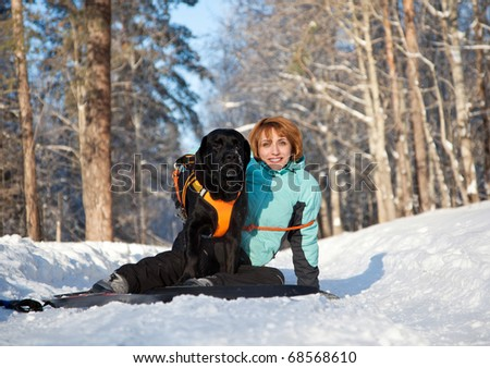 The young woman with dog in winter wood - stock photo