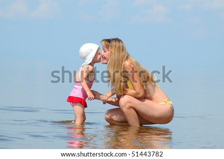 The young woman with the little girl concern with noses on a beach