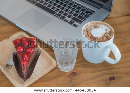 The Young woman works at the laptop with cake and coffee - stock photo