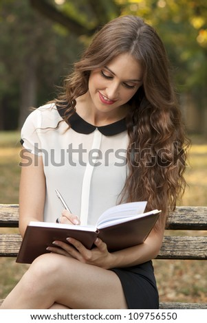 The young woman writes something in her book - stock photo