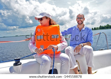 The young women  wears bright orange life-jacket and fashion man on yacht. - stock photo