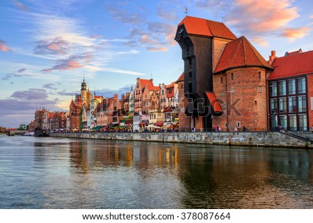 The Zuraw Crane and colorful gothic facades of the old town in Gdansk, Poland, on sunset - stock photo