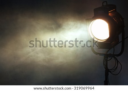 theater spot light with smoke against grunge wall - stock photo