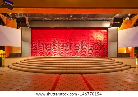 Theater stage with red curtains and steps. Theatrical scene,  the interior of the old theater of the luxury caribbean resort. Bahia Principe, Riviera Maya, Mexican Resort. - stock photo