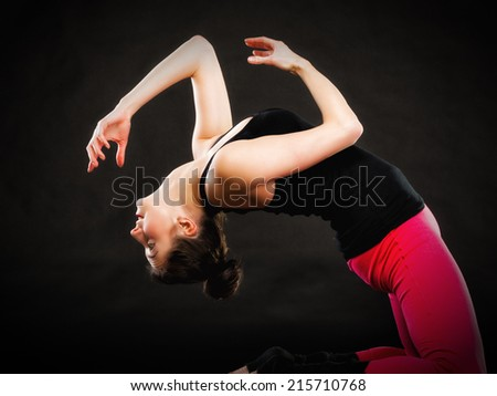 Theatrical art. Brunette girl actress doing acting exercise on black. Woman performing on theater stage. - stock photo