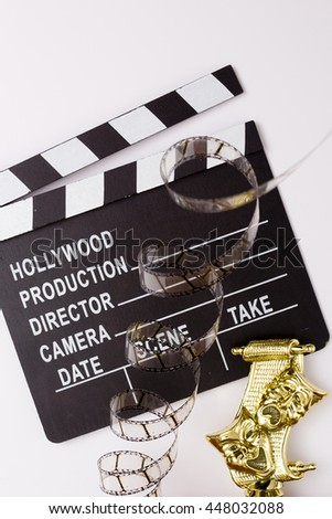Theatrical masks, party poppers and film for cinema on a white background - stock photo