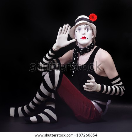 Theatrical mime in white hat with red flower sits on the floor - stock photo