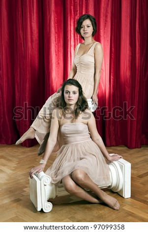 Theatrical portrait of two women in evening dresses, sitting on two hellenic ionic columns on a stage in front of a red curtain - stock photo