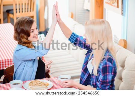 Their friendship will last a lifetime. Two young beautiful female friends sitting in cafe and laughing while joining their palms together  - stock photo