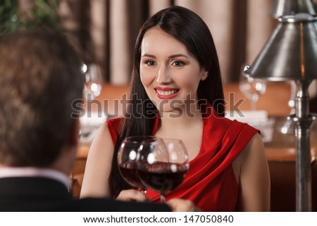 Their special date. Beautiful mature couple drinking wine at restaurant and looking at each other - stock photo