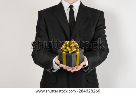 Theme holidays and gifts: a man in a black suit holds exclusive gift wrapped in a black box with gold ribbon and bow isolated on a white background in studio - stock photo